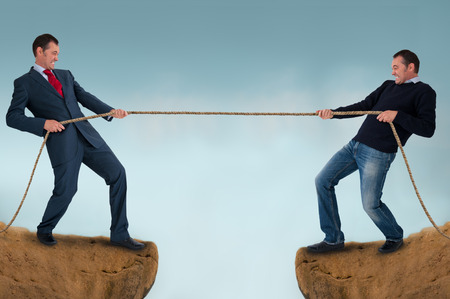 tug of war men pulling rope over a crevasse