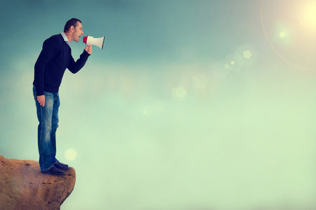 chasm: man with a loudhailer or megaphone shouting from edge of a cliff