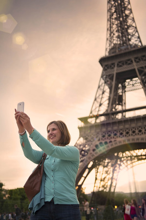 mature woman taking a selfie with the eiffel tower paris photo