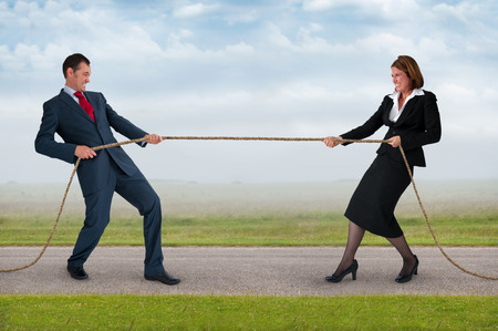 businessman and businesswoman tug of war contest of strength