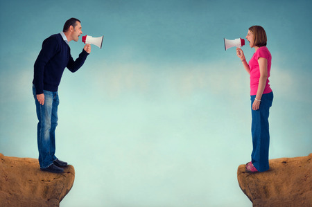 deadlock: man and woman conflict concept with bullhorn and crevasse Stock Photo