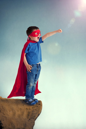 in the edge: superhero boy child standing on a cliff edge Stock Photo
