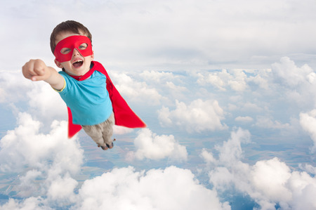 superhero boy child flying mid air above cloud level Foto de archivo