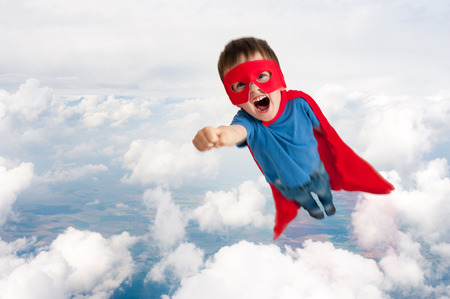 dressing up costume: superhero boy child flying upwards through the clouds