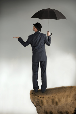 business protection: business protection concept businessman with umbrella feeling for rain