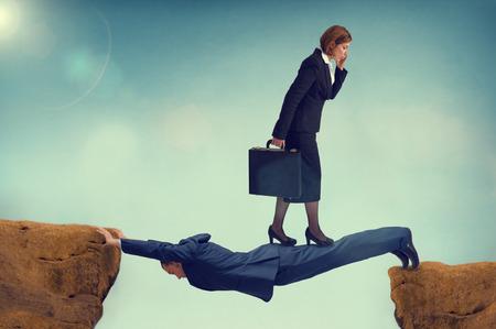 dominacion: Mujer de negocios despiadado caminando sobre un hombre de negocios vulnerables Foto de archivo