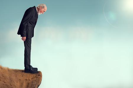 senior man op zoek naar beneden van een klif Stockfoto