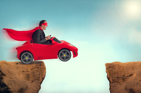 man in a red car jumping a ravine
