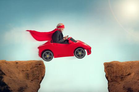 onward: active senior superhero driving a car off a ravine Stock Photo