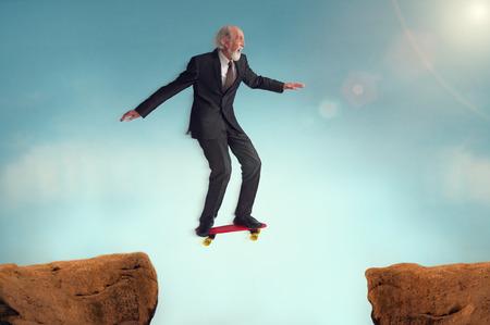 gente saltando: Hombre mayor disfrutando el riesgo de un desaf�o de salto en patineta Foto de archivo