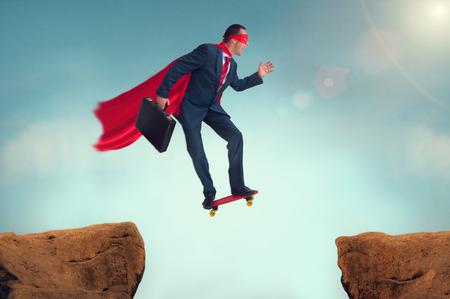スケート ボードで信仰の危険な飛躍を作るスーパー ヒーロー実業家