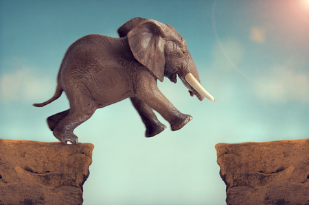 challenges: leap of faith concept elephant jumping across a crevasse