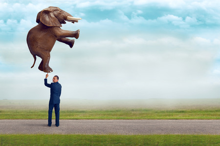 elefant: Geschäftsmann hält einen Elefanten mit einem Finger subtile Vintage-Filter und selektiven Fokus mit Kopie Raum