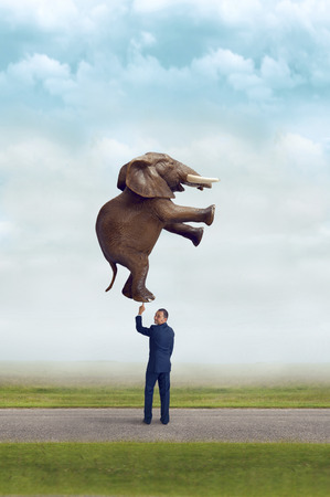 zakenman die een olifant met één vinger subtiele vintage filter en selectieve aandacht met kopie ruimte Stockfoto