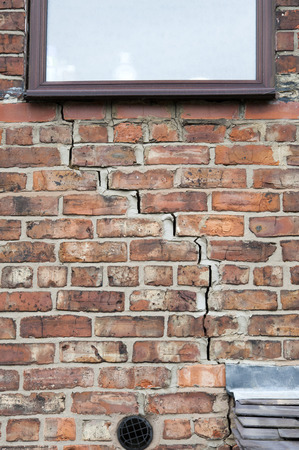 heave: step cracking damage to brickwork in a wall beneath a window as a result of subsidence