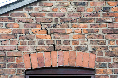 침하의 결과로 창 위에있는 벽에 벽돌 세공에 균열이 생기는 단계 스톡 콘텐츠