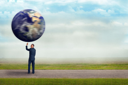 lifting globe: businessman holding spinning planet earth aloft with one finger subtle vintage filter and selective focus with copy space