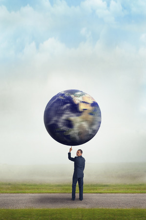 aloft: businessman holding spinning planet earth aloft with one finger subtle vintage filter and selective focus with copy space