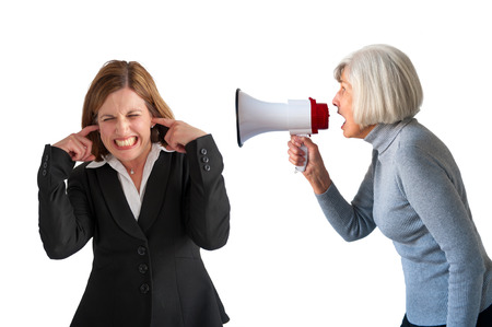 deafening: mature woman being shouted at by senior woman on white Stock Photo