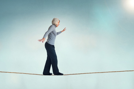 senior woman walking on a tightrope