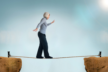 daunting: senior woman walking on a tightrope