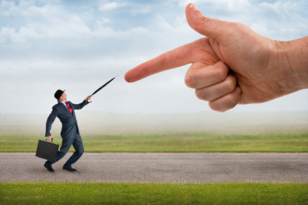 fend: giant finger pointing aggressively at a defensive businessman Stock Photo