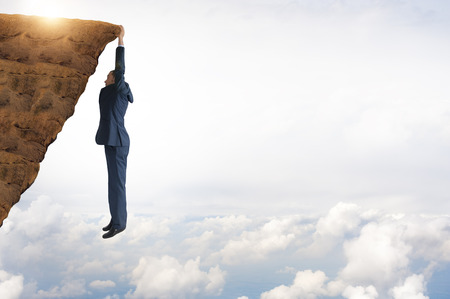 business concept challenge businessman clinging on