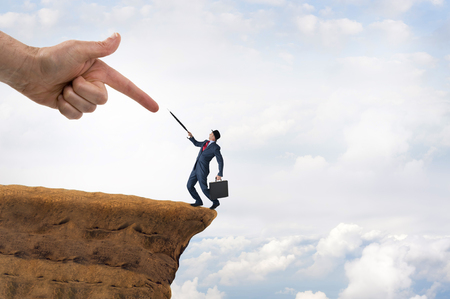 edge of cliff: business challenge concept businessman pushed to the edge of a cliff