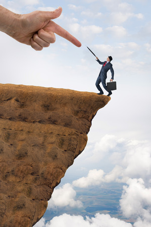 pushed: business challenge concept businessman pushed to the edge of a cliff