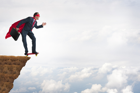 speculate: business bravery courage concept superhero businessman leaping off a cliff on a skateboard Stock Photo
