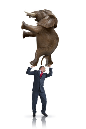 metaphors: business balance challenge concept businessman holding weight of elephant above his head