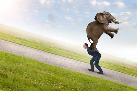 upward struggle: business adversity concept with businessman carrying elephant uphill