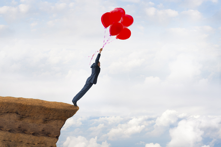 business freedom concept courageous daring businessman flying off a cliff holding faith in balloons Stock Photo