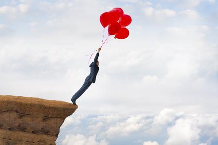Business-Freiheit-Konzept mutig gewagt Unternehmer, die eine Klippe hält den Glauben an Ballons fliegen weg