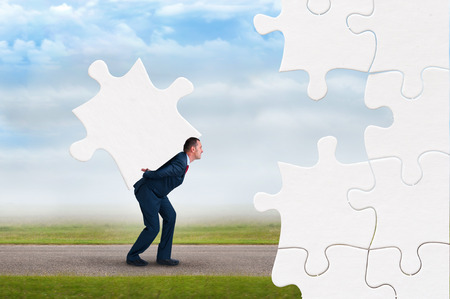 solve: business puzzle concept businessman faces adversity to solve jigsaw Stock Photo
