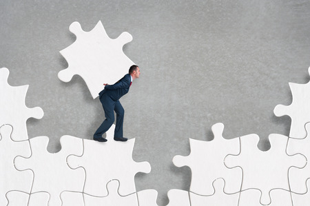 businessman struggling to complete a jigsaw puzzle alone 版權商用圖片