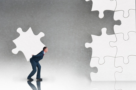 business puzzle concept businessman working to complete a jigsaw 版權商用圖片