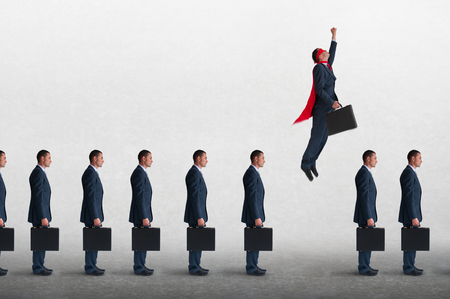 superhero businessman overcoming inertia flying away from a static queue of businessmen Stok Fotoğraf - 81962052