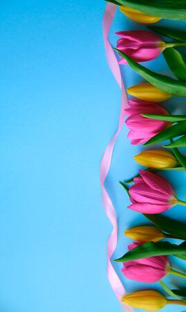 colourfull flowers with pink ribbon on blue background, copyspace, postcard, label concept, vertical shot