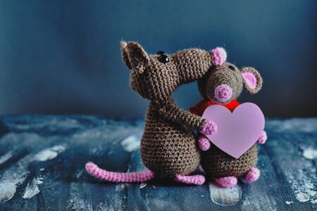 Handcrafted amigurumi rat hugs another knitted toy rat that holds the pink heart as a present. Valentine day, February 14, love, relations concept.
