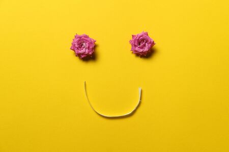 smiley face made out of rose flowers and ribbon, spring blossom concept, happy, yellow background