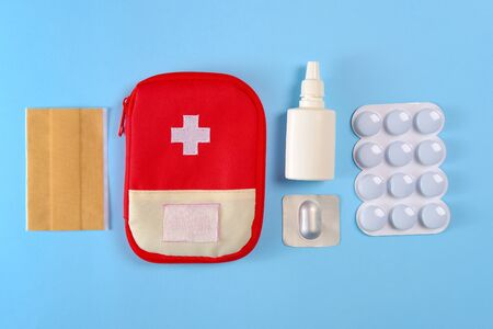 Closed tourist first aid kit pouch near to the pills, adhesive bandages and nasal spray on the bright blue background.
