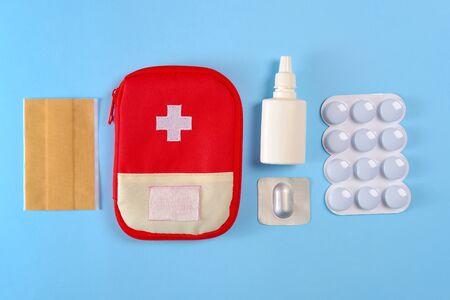Pochette de trousse de premiers soins touristiques fermée près des pilules, des pansements adhésifs et du spray nasal sur le fond bleu vif.