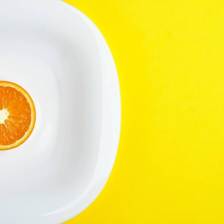 Top view of the sliced orange at the white dish lies on the bright yellow background. Healthy food, detox, diet concept.