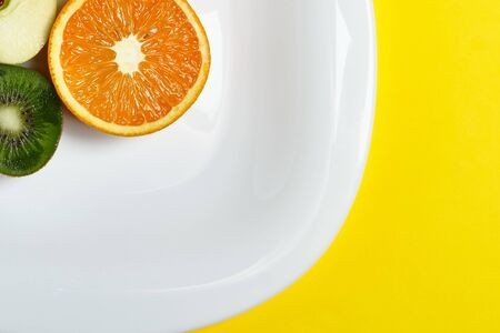 Top view of the sliced orange apple and kiwi fruit at the white dish lies on the bright yellow background. Healthy food, detox, diet concept.