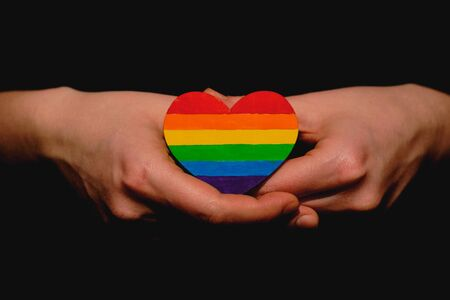 Female arms holding the heart coloured in LGBT pride colours on the dark background. Concept of the International Day Against Homophobia concept, sexual equality, feminism, social safety. Stock Photo