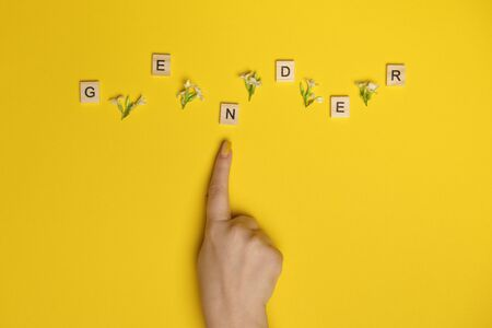 Word gender depicted by using wooden blocks and flowers on yellow bee background with woman hand pointing on it