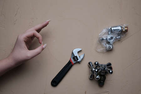 Girl hand showing OK sign with a table full of plumbing tools and partsch. Tool for plumbing repair with their hands on table Stock fotó
