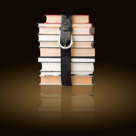 many books pile with black leather belt photo