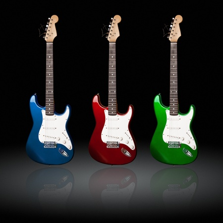 stratocaster: three electric guitars of different colors with reflections  Stock Photo